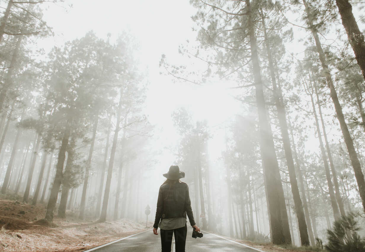 back-view-of-traveling-photographer-woman-standing-on-road-in-foggy-forest-with-photo-camera-A...jpg